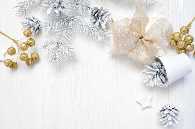 Makieta prezent na boże narodzenie złoty łuk i stożek drzewa, flatlay na białym Premium Zdjęcia