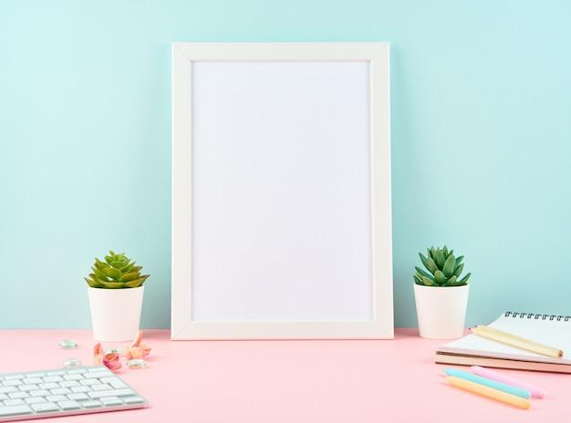 Makieta pusta biała ramka, alarm, notatnik, klawiatura na różowym stole o niebieską ścianą z kopią. nowoczesny jasny biurowy pulpit Premium Zdjęcia