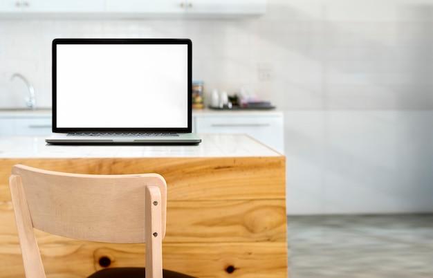Makieta pusty ekran laptopa na drewnianym stole w pokoju kuchnia Premium Zdjęcia