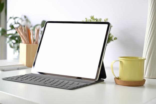 Makieta pusty ekran tablet i inteligentna klawiatura na białym stole Premium Zdjęcia