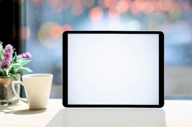 Makieta pusty ekran tablet z białym kubkiem na białym drewnianym stole Premium Zdjęcia