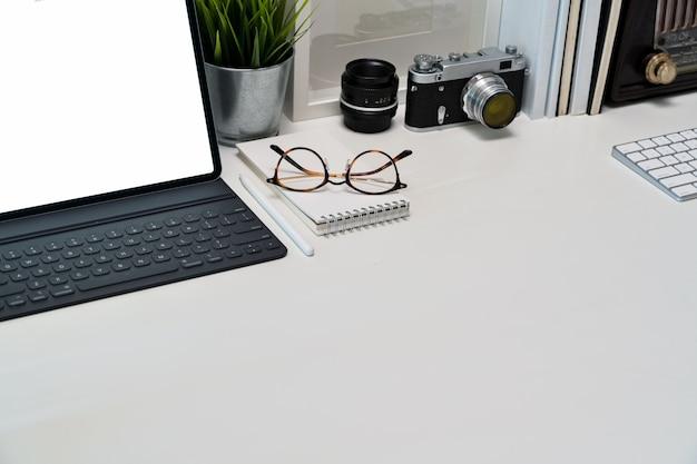 Makieta pusty ekran tabletu, plakat, książki i rocznika kamery na obszarze roboczym Premium Zdjęcia