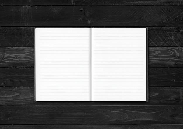 Makieta Pusty Notatnik Otwarty Na Białym Tle Na Czarnym Tle Drewna Premium Zdjęcia