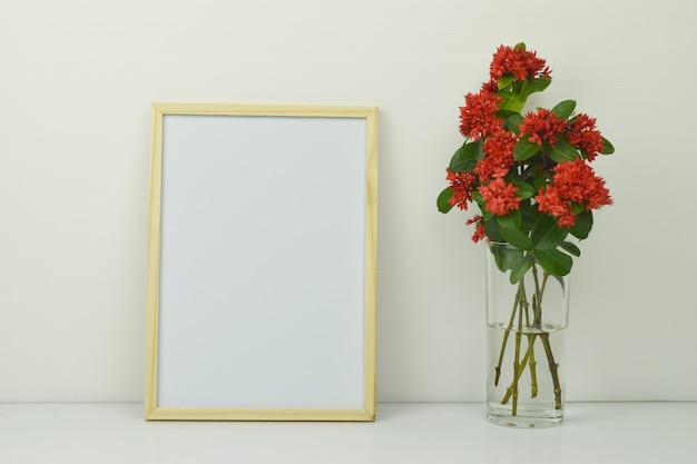 Makieta ramki z czerwonymi kwiatami kolców w przezroczystym szklanym wazonie na białym tle. Premium Zdjęcia