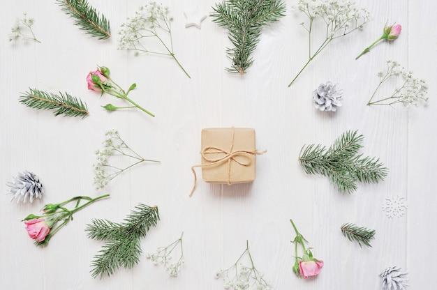 Makieta świąteczna kompozycja. prezent na boże narodzenie, kwiaty, szyszki Premium Zdjęcia