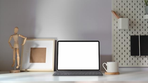 Makieta tablet z inteligentną klawiaturą na minimalnym stole roboczym. Premium Zdjęcia