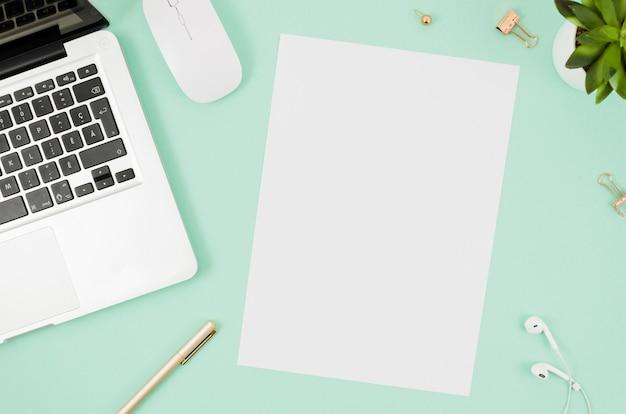 Makieta z papieru płaskiego leżącego obok laptopa Darmowe Zdjęcia