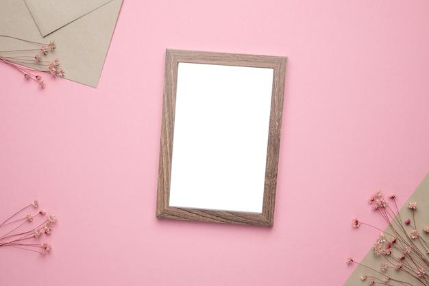 Makieta Zdjęcia W Drewnianej Ramie Z Suchym Kwiatem Na Różowym Tle Widok Z Góry Premium Zdjęcia