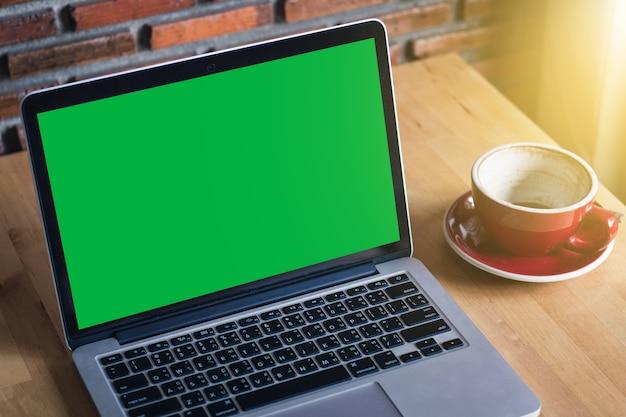Makiety monitor laptopa zielony ekran na drewnianym stole Premium Zdjęcia