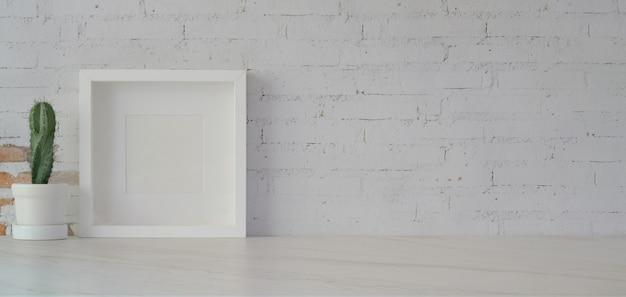 Makiety ramki z doniczki kaktusa w minimalnym pokoju biurowym na białym stole i białym murem Premium Zdjęcia