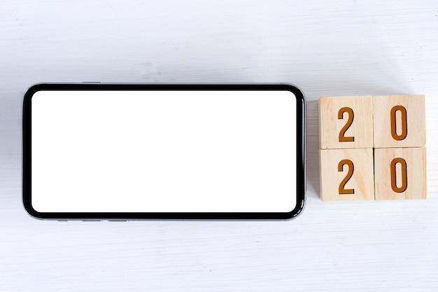 Makiety Smartfona I Drewniane Kostki Z Numerami Symbolizującymi Nowy Rok Premium Zdjęcia
