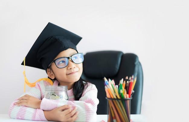 Mała azjatycka dziewczyna jest ubranym absolwenta kapeluszowego przytulenie jasnego szklanego słój Premium Zdjęcia