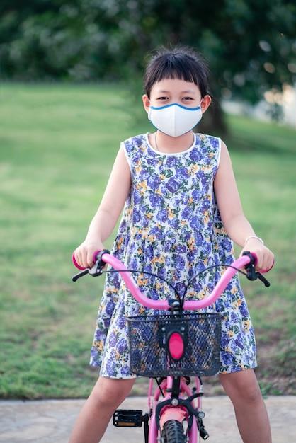 Mała Azjatycka Dziewczyna Ma Na Sobie Maskę I Jedzie Na Rowerze Na Zewnątrz Z Uśmiechem I Radością Premium Zdjęcia