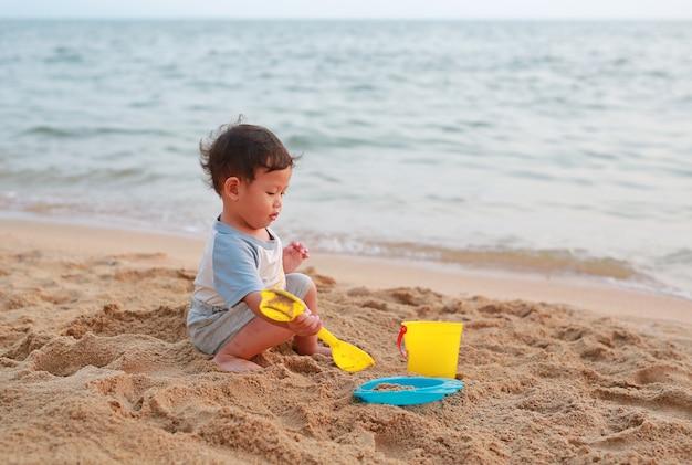 Mała Azjatykcia Chłopiec Bawić Się Piasek Przy Plażowy Samotnie. Premium Zdjęcia
