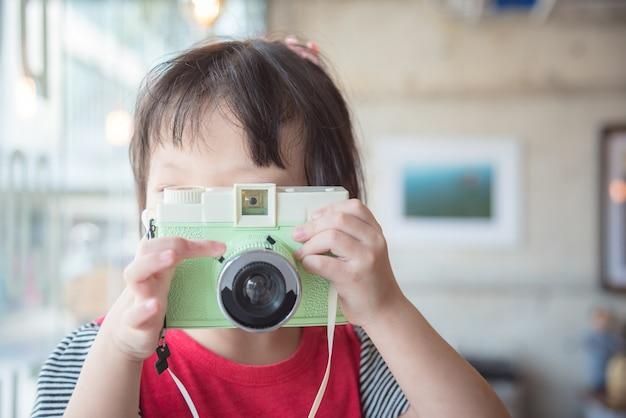 Mała azjatykcia dziewczyna bierze fotografię klasyczną kamerą w kawiarni Premium Zdjęcia