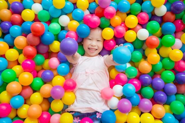 Mała azjatykcia dziewczyna ono uśmiecha się podczas gdy kłamający na wiele kolor piłce przy indoors boiskiem Premium Zdjęcia