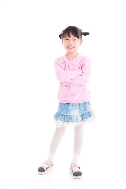 Mała Azjatykcia Dziewczyny Pozycja, Uśmiechy Nad Białym Tłem I Premium Zdjęcia
