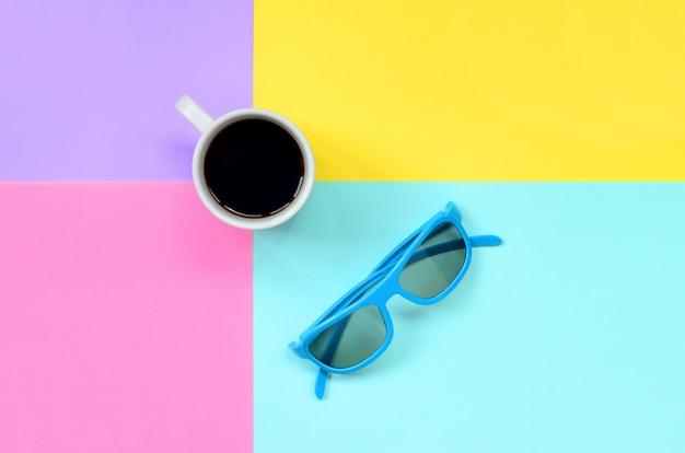 Mała biała filiżanka i błękitni okulary przeciwsłoneczni na tekstury tle Premium Zdjęcia