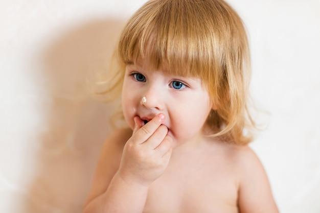 Mała Blondynka Dziewczynka W Różowe Spodnie Siedzi Na Białym Stole, Jedzenie Tort Urodzinowy Premium Zdjęcia