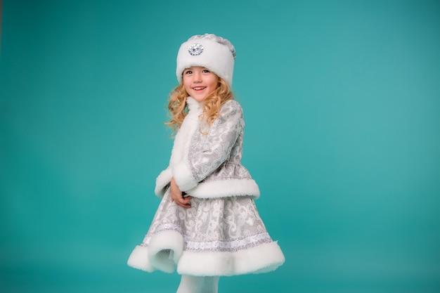Mała blondynka uśmiecha się w stroju dziewicy śniegu izolować na niebieską ścianą Premium Zdjęcia