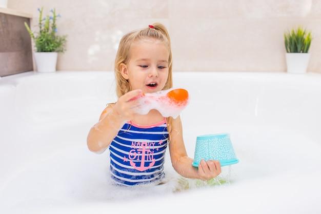 Mała Blondynki Dziewczyna Bierze Bąbla Skąpanie W Pięknej łazience. Dzieci Higiena. Szampon, Pielęgnacja Włosów I Mydło Dla Dzieci. Dziecko Kąpie Się W Dużej Wannie. Premium Zdjęcia