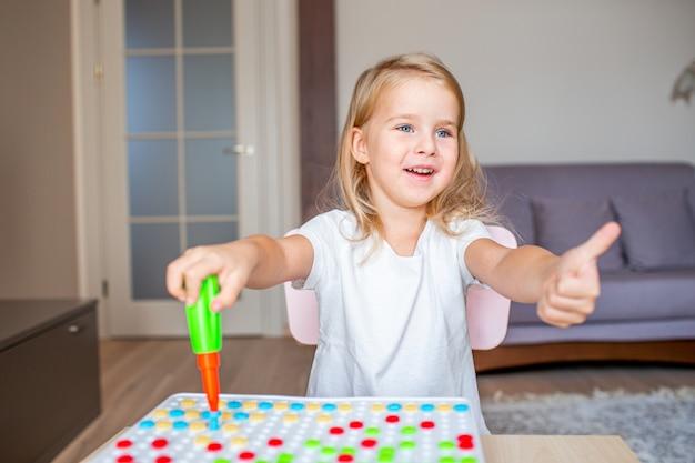 Mała Blondynki Dziewczyna Siedzi Przy Stołem W Domu Bawić Się Z Zabawkarskim śrubokrętem I Multicolor śrubami. Wczesna Edukacja. Premium Zdjęcia