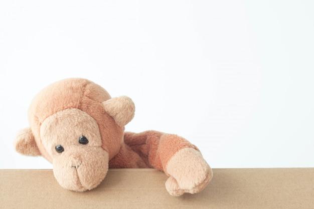 Mała Brąz Małpa Z Biel ścianą. Uśmiechał Się Radośnie Premium Zdjęcia