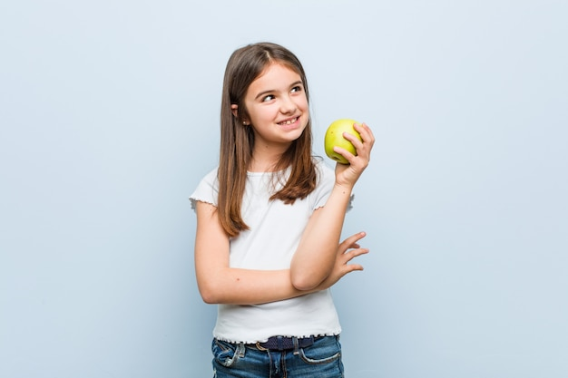 Mała caucasian dziewczyna trzyma zielonego jabłka ono uśmiecha się ufny z krzyżować rękami Premium Zdjęcia