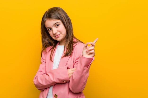 Mała Caucasian śliczna Dziewczyna Ono Uśmiecha Się Radośnie Wskazujący Z Palcem Wskazującym Daleko Od. Premium Zdjęcia