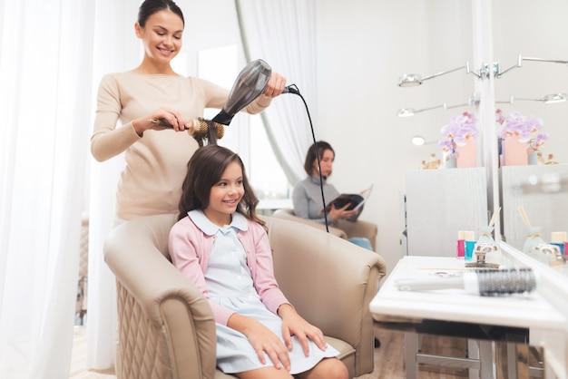 Mała ciemnowłosa dziewczyna siedzi w fotelu w salonie piękności Premium Zdjęcia