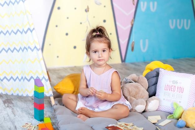 Mała Dziewczynka Bawi Się Na Podłodze Z Kolorowych Kostek. Dziecko Bawi Się Zabawkami W Pokoju Dziecięcym. Mała Dziewczynka Gra W Przedszkolu. Koncepcja Dzieciństwa, Rozwój Dziecka. Szczęśliwe Dziecko Bawi Się Z Bloków. Premium Zdjęcia