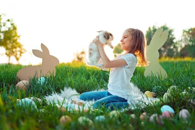Mała Dziewczynka Bawi Się Z Królikiem W Otoczeniu Pisanek Premium Zdjęcia