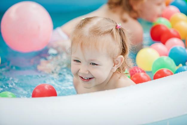 Mała Dziewczynka Bawi Się Zabawkami W Nadmuchiwanym Basenie W Słoneczny Letni Dzień Darmowe Zdjęcia