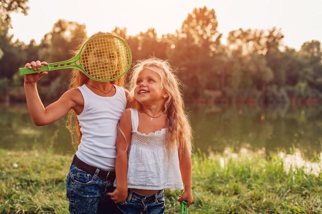Mała dziewczynka bawić się badminton z siostrą w lato parku Premium Zdjęcia