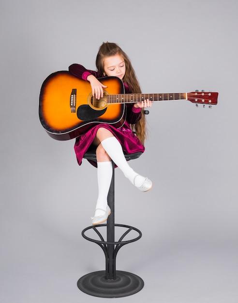 Mała dziewczynka bawić się gitarę akustyczną na prętowym krześle Darmowe Zdjęcia