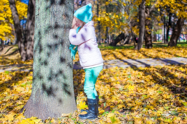 Mała dziewczynka bawić się w chowanego blisko drzewa w jesień parku Premium Zdjęcia