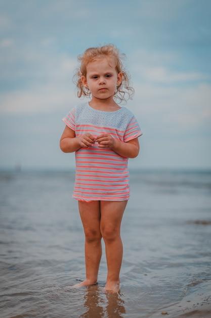 Mała dziewczynka bawić się w fala przy morzem Premium Zdjęcia