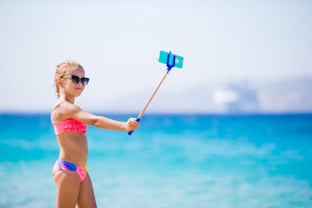 Mała Dziewczynka Bierze Autoportret Jej Smartphone Na Plaży. Dzieciak Cieszy Się Swoimi Wakacyjnymi Wakacjami I Robi Zdjęcia Na Pamiątkę Premium Zdjęcia