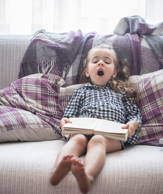 Mała Dziewczynka Czytanie Książki Na Kanapie Darmowe Zdjęcia