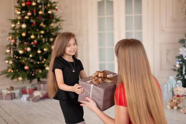 Mała Dziewczynka Daje Mamie Pudełko Z Prezentem świątecznym. Premium Zdjęcia