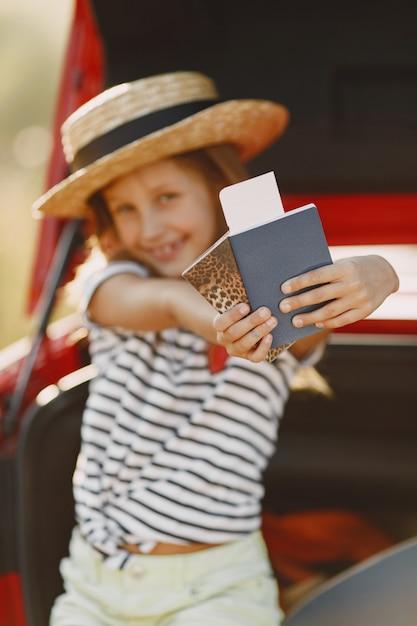 Mała Dziewczynka Gotowa Na Wakacje. Dziecko Siedzi W Samochodzie Bada Mapę. Dziewczyna Z Paszportem. Darmowe Zdjęcia