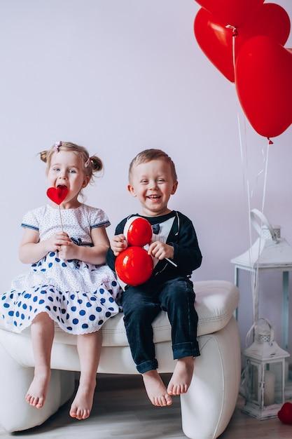 Mała Dziewczynka I Chłopiec Siedzi Na Białym Krześle W Pobliżu Balony W Kształcie Serca. Dziewczyna Liże Czerwonego Lizaka. Koncepcja Walentynki. Premium Zdjęcia