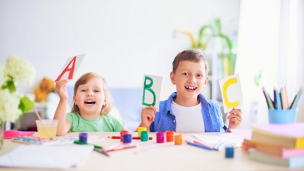 Mała dziewczynka i chłopiec uczą się w domu. Premium Zdjęcia