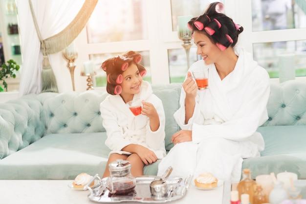 Mała dziewczynka i jej matka siedzą na kanapie Premium Zdjęcia