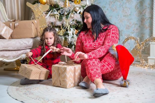 Mała Dziewczynka I Matka Otwierając Prezenty W Pobliżu Choinki. Premium Zdjęcia