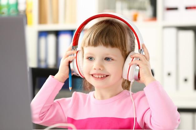 Mała Dziewczynka Jest Ubranym Hełmofony Używa Mobilnego Komputer Premium Zdjęcia