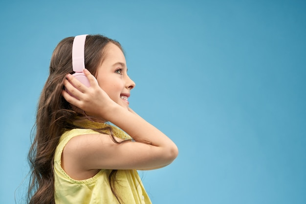 Mała Dziewczynka Jest Ubranym Słuchawki, Słucha Muzykę I Ono Uśmiecha Się Darmowe Zdjęcia