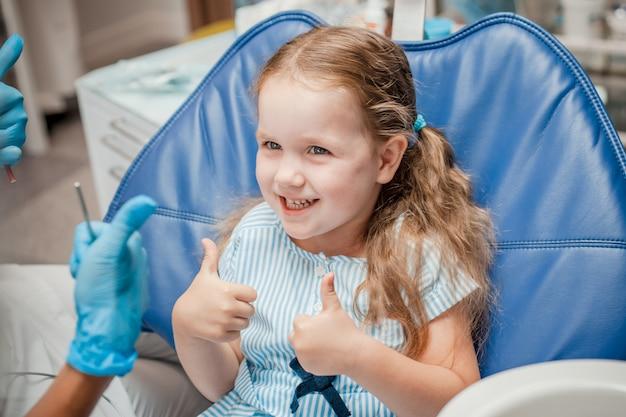 Mała dziewczynka jest zadowolona z końca leczenia u dentysty Premium Zdjęcia