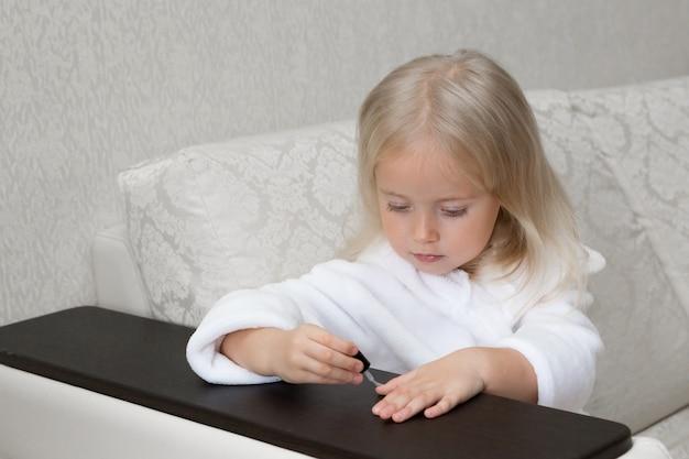 Mała Dziewczynka Kaukaska Maluje Paznokcie Na Rękach. Premium Zdjęcia