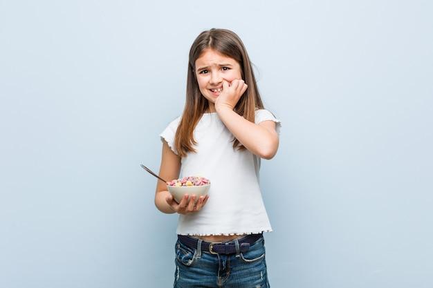 Mała Dziewczynka Kaukaski Trzyma Miskę Zbożową Obgryzanie Paznokci, Nerwowy I Bardzo Niespokojny. Premium Zdjęcia